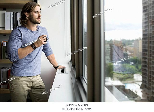 Pensive businessman drinking coffee looking out office window
