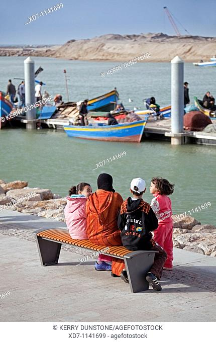 Morocco Rabat Riverfront with moored fishing boats watched by young family