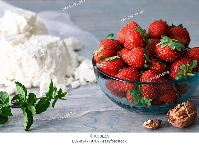 A glass bowl full of fresh ripe strawberries, homemade cottage cheese and a mint twig on a blue wooden background