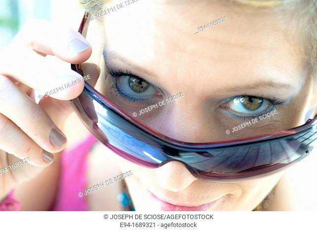 41 year old blond woman looking over her sun glasses