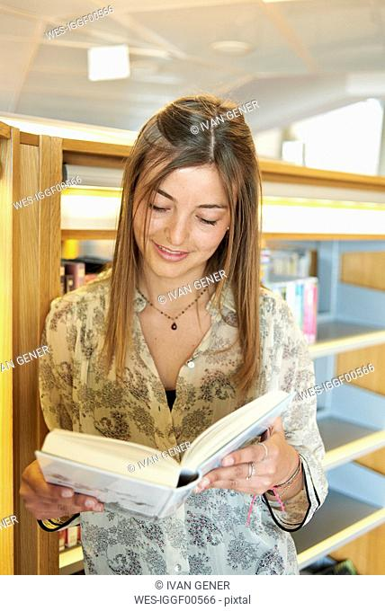 Portrait of smiling young woman with book at the library