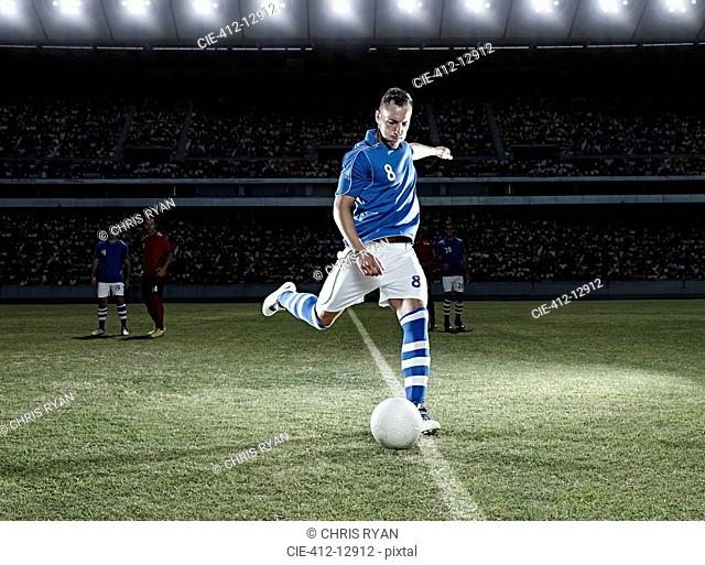 Soccer player kicking ball on field