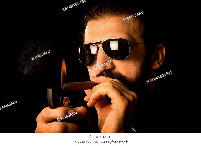 The elegant gentleman in sunglasses is igniting his cigar with zippo on black background