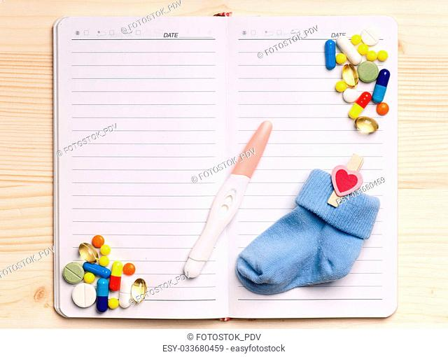 Blank notepad with pregnant test on the wooden table. View from above