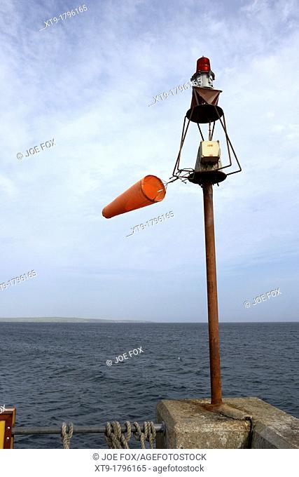 windsock flying on a harbour light mast in high winds John O'Groats scotland uk