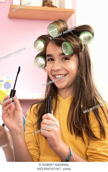 Girl with hair roller holding mascara, smiling, portrait