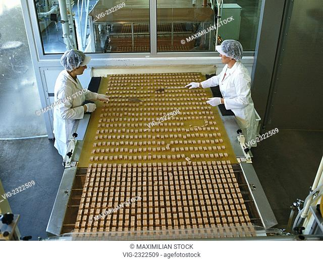Chocolate plant. Women working by a conveyer belt and checking the quality of chocolate bars - 01/01/2010