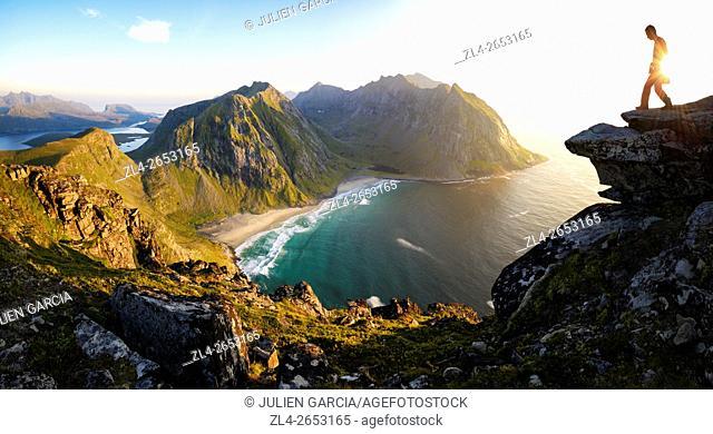 Norway, Nordland, Lofoten islands, Moskenesoy island, hiker at the summit of mount Ryten (543m), the isolated beach of Kvalvika below