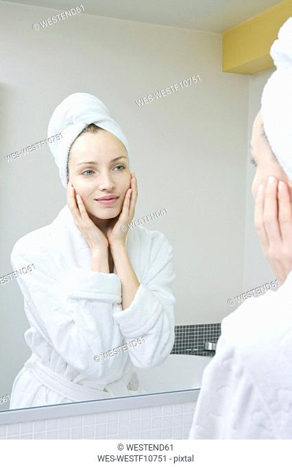 Young woman looking in mirror, portrait