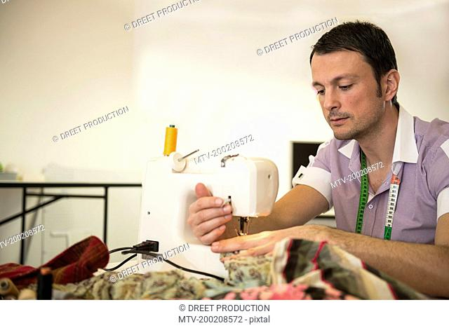 Male dressmaker stitching cloth on sewing machine, Bavaria, Germany