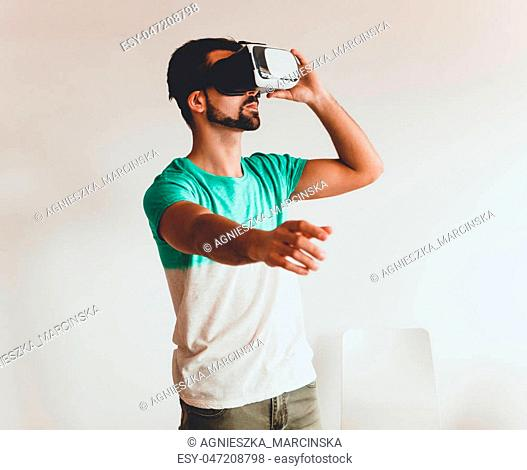 Young bearded man wearing virtual reality. Smartphone using with VR goggles headset
