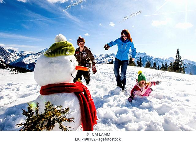Mother and two children in snow near a snowman, Planai, Schladming, Styria, Austria