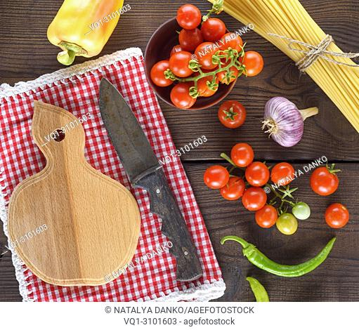 empty wooden cutting board with a knife and fresh red cherry tomatoes, beside a tied bundle of long raw spaghetti