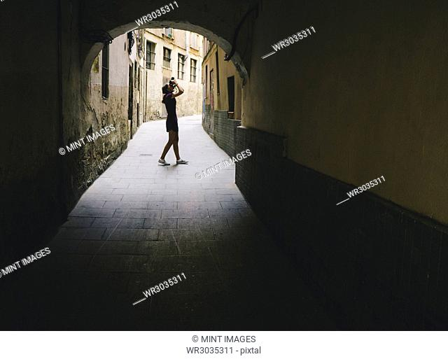 Teenage girl composing photo with digital camera, Gothic Quarter, Barcelona, Spain