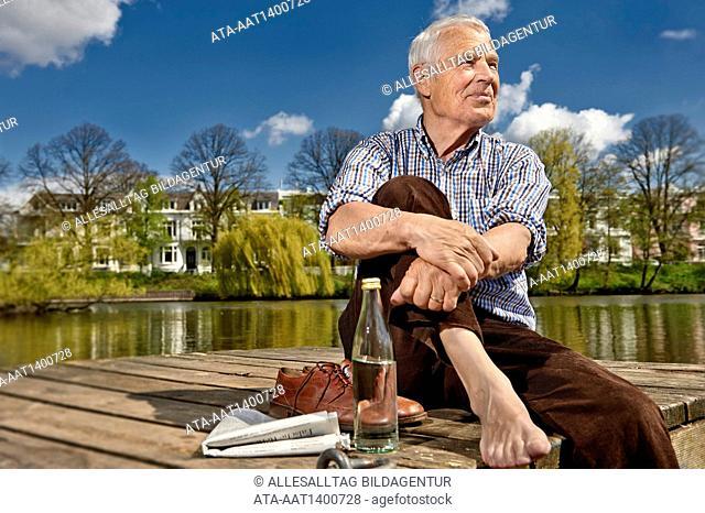 Senior sitting on a boardwalk in summer