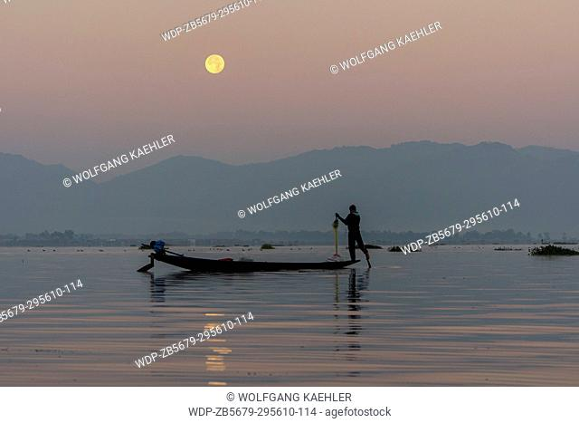 Before sunrise under a full moon a leg-rowing fisherman in his boat is pulling in his fishing net he set the day before on Inle Lake in Myanmar