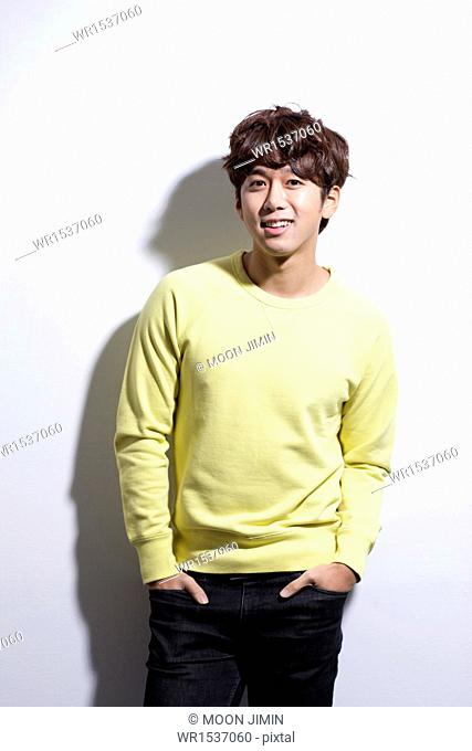 a man wearing a yellow sweater posing happily