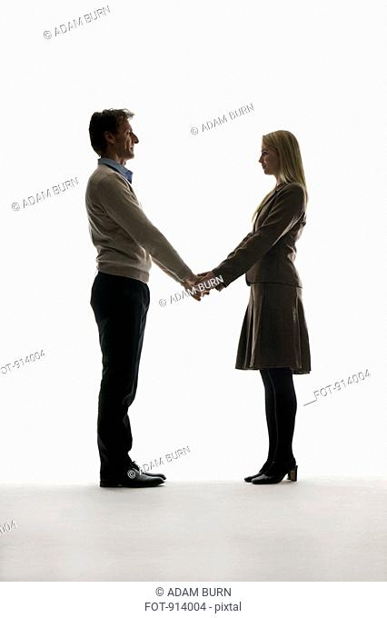 A boyfriend and girlfriend holding hands, face to face