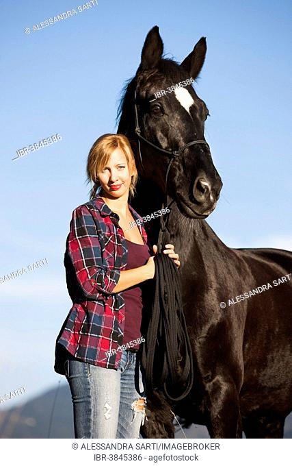 A young woman with a black Hanoverian horse, North Tyrol, Austria