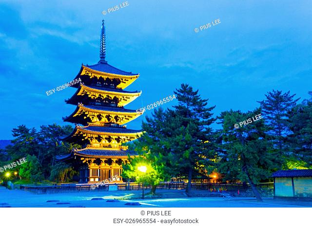 Dramatic blue sky and lighted five story pagoda, goju-no-to, at evening blue hour in Kofuku-ji temple complex in historic Nara, Japan. Horizontal