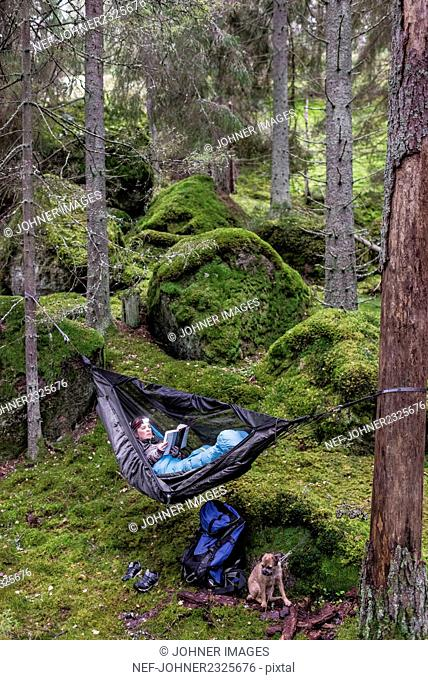 Woman reading book in hammock in forest