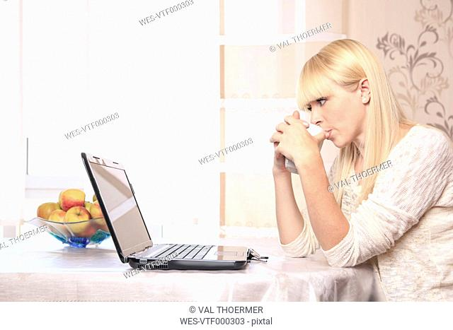 Portrait of a young woman with a cup using laptop at home