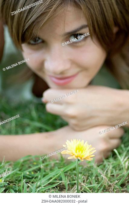 Young woman lying in grass by yelllolw flower