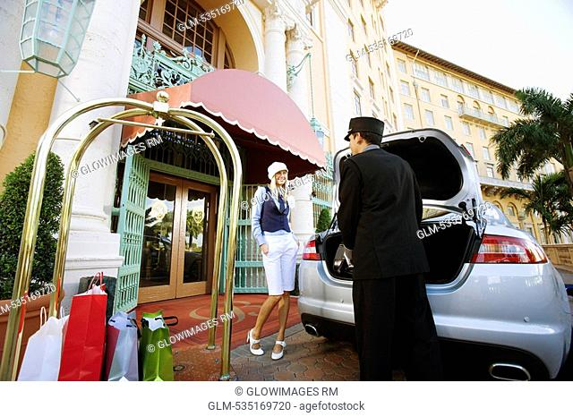 Hotel porter carrying luggage with a woman standing, Biltmore Hotel, Coral Gables, Florida, USA