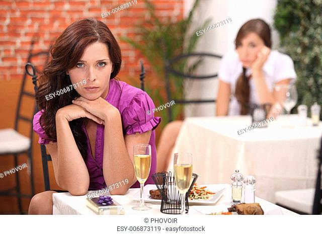 angry woman at the restaurant, on the table, an unopened gift and flutes of sparkling wine