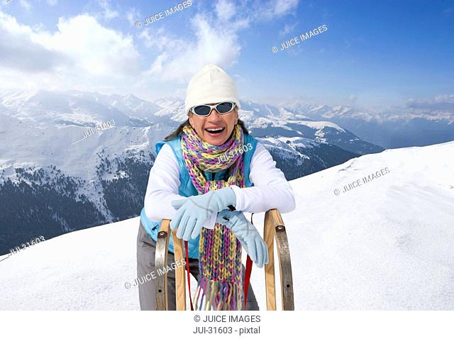 Portrait of smiling woman leaning on sled on snowy mountain