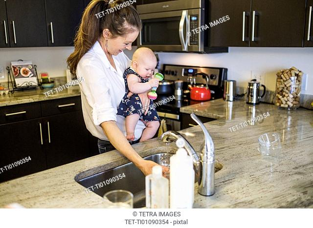 Mother holding baby daughter (2-5 months) and filling glass with water