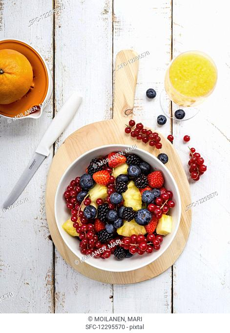 A bowl of fruit salad with blueberries, strawberries, blackberries, redcurrants and pineapple and a glass of mimosa next to it