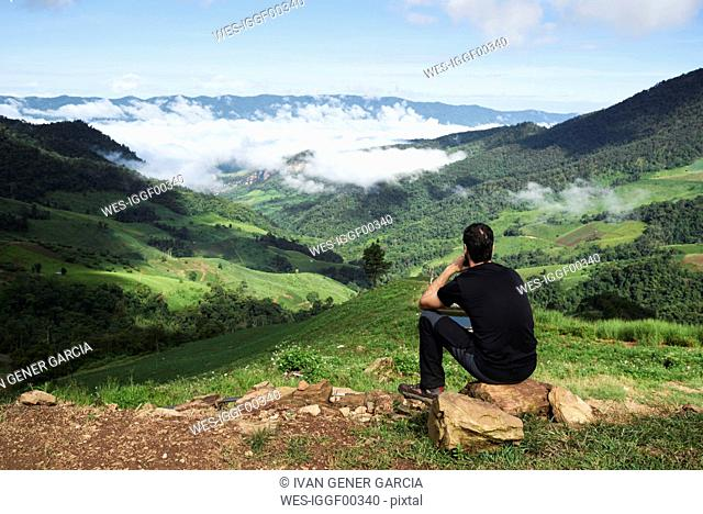 Thailand, Phu Chi Fa, traveler sitting at the top of a hill with view over rice fields