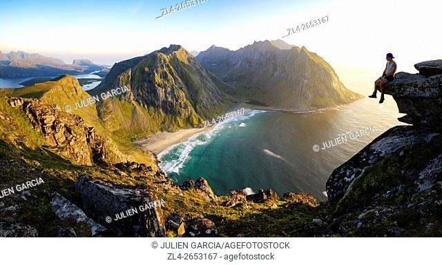 Norway, Nordland, Lofoten islands, Moskenesoy island, hiker at the summit of mount Ryten (543m), the isolated beach of Kvalvika below, Model Released