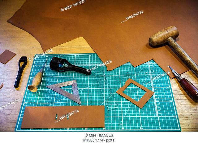 Workbench and cutting mat with a large smooth piece of brown leather, and tools for measuring cutting and stitching, leatherworking tools