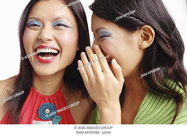 Two women, one laughing, the other whispering in her ear