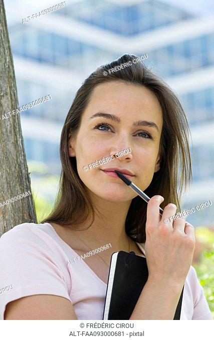 Woman holding notebook and pen, looking up in thought