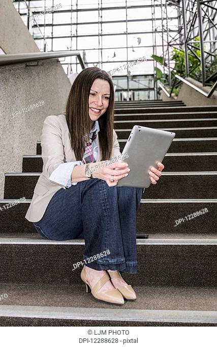 Mature business woman sitting on stairway in the atrium of an office building looking at her tablet; Edmonton, Alberta, Canada