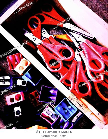 Box of red handled scissors and coloured pencil sharpeners