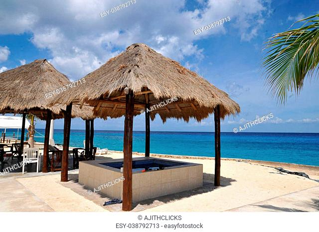 Exotic beach with palm tree umbrellas, golden sand, azure water and blue sky