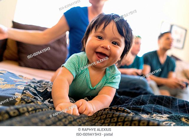 Baby smiling widely on sofa, family in background