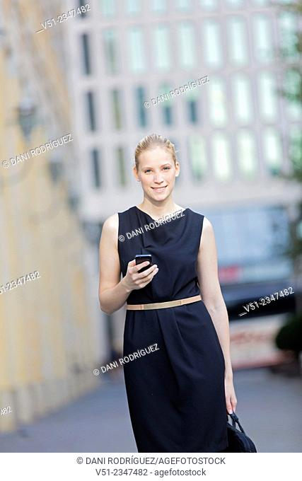 Portrait of a businesswoman in downtown with mobile phone looking at camera