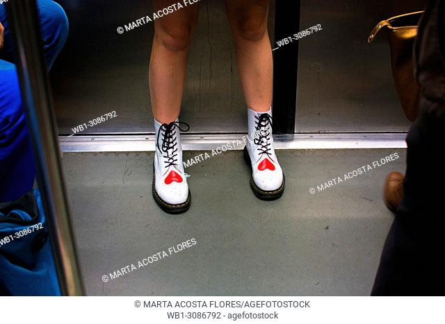 Legs of a girl wearing white boots with a red heart print in the underground of Paris. France