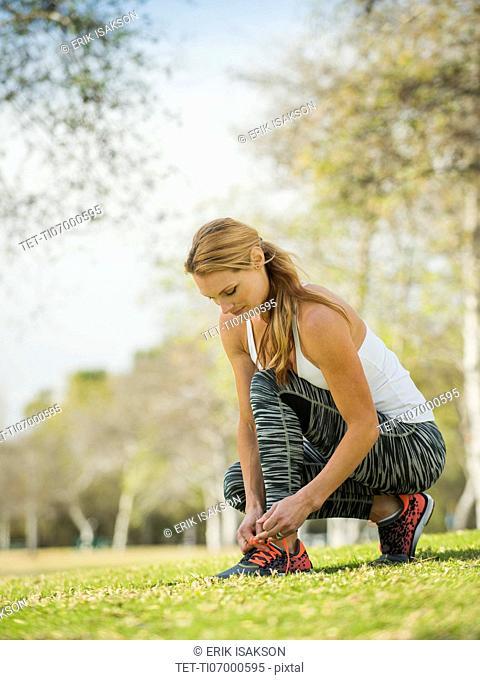 Woman in park tying shoe