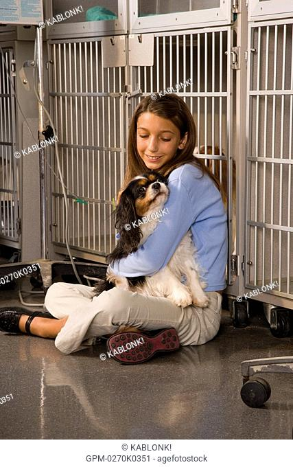 Girl comforting pet dog in veterinary clinic