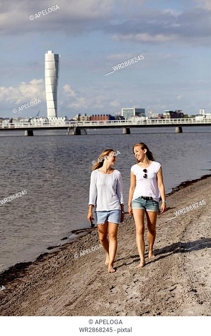 Smiling female friends walking on shore with Turning Torso in background