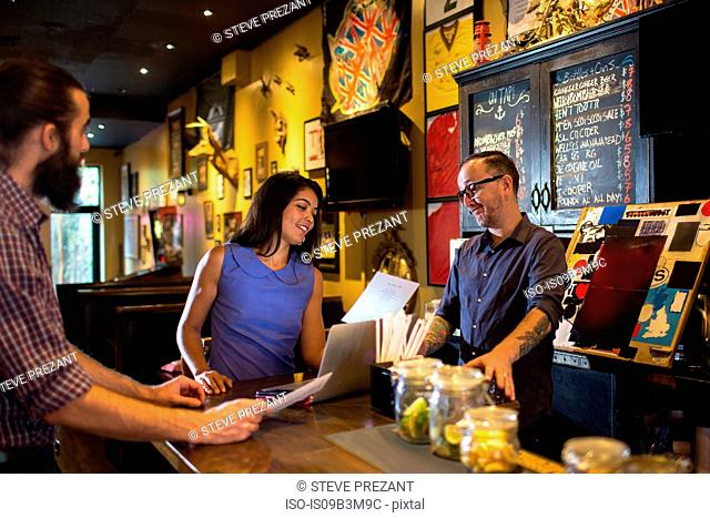Barman reading menu with young couple at public house counter