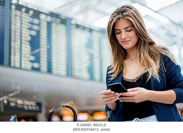 Young woman using cell phone at departure board looking around