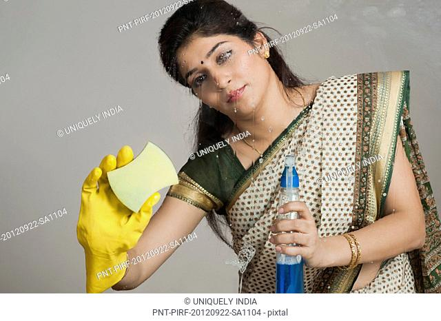 Woman cleaning a glass with cleaning fluid and sponge