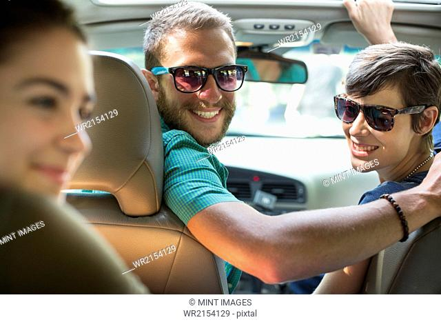 A group of people inside a car, on a road trip. View from the back seat